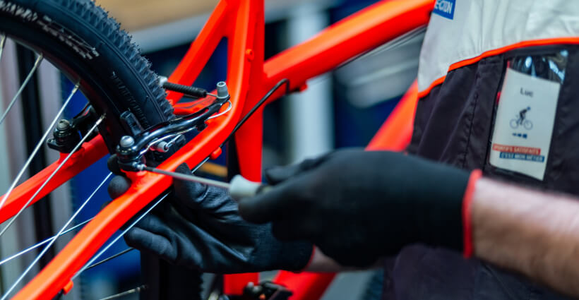 Photo d'un technicien Decathlon en train de réparer un vélo en atelier